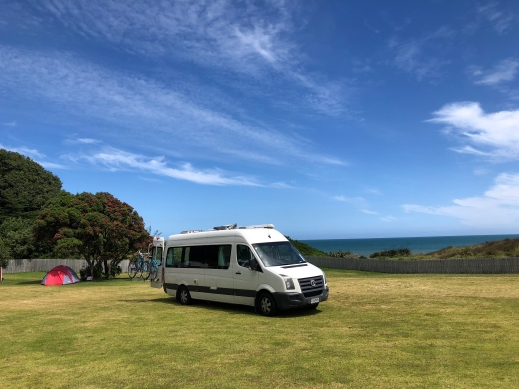 Kiwi Blog Bus campervan parked at Ohawe Beach Campsite
