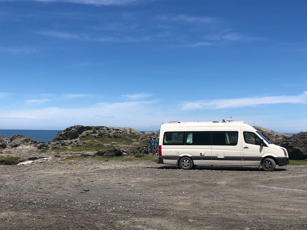 Kiwi Blog Bus Campervan parked near rocky foreshore at Cape Palliser