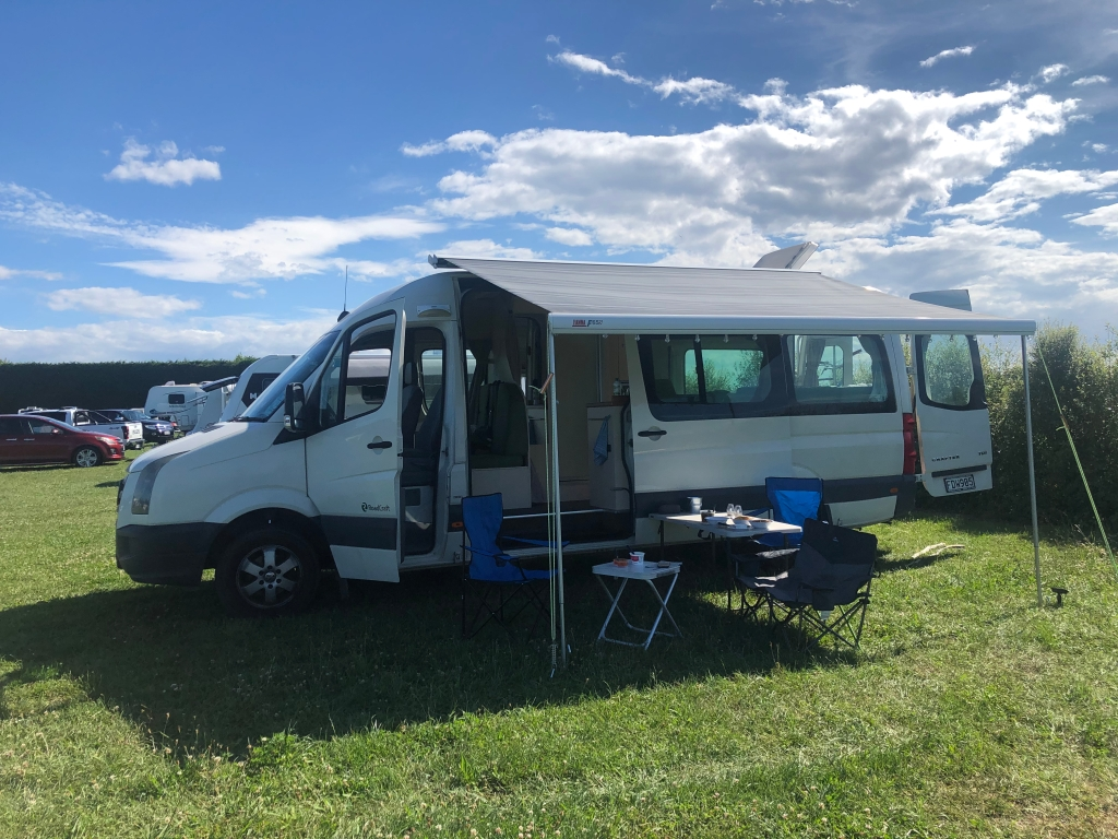 The Kiwi Blog Bus Campervan parked up on a campsite with awning and furniture out